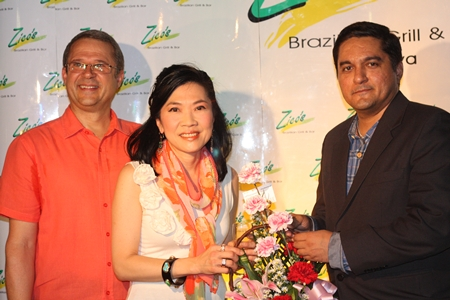 Kamolthep (Prince) Malhotra, right, General Manager of Pattaya Mail Publishing Co., Ltd. offers congratulations and presents a bouquet of flowers to Centara's Supatra Chirathivat and Andre Brulheart.