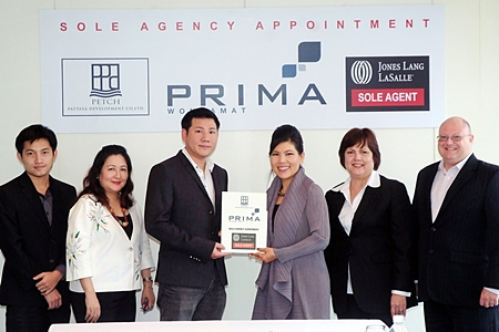 Itthi Chavalittamrong (3rd left), CEO of Petch Pattaya Development Co., Ltd, holds up the contract of appointment of Jones Lang LaSalle as the sole sales agent for Prima Wongamat with Suphin Mechuchep (3 right), Managing Director of Jones Lang LaSalle.