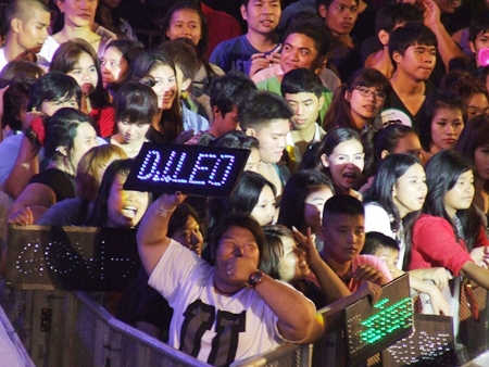 Spectators in front of stages holding electric signs cheer for their favorite musicians.