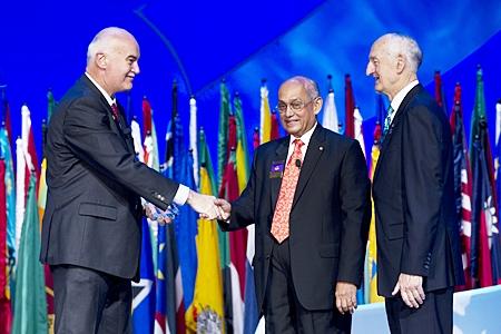 R.I. President Kalyan Banrjee congratulatesJohn Skerritt (left) as he receives the 2011-12 Global Alumni Service to Humanity Award from Rotary Foundation Trustee Chair William B. Boyd.