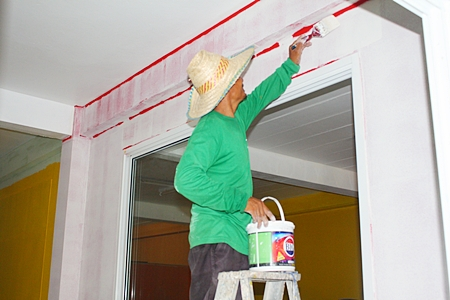 An ESC worker prepares a base coat before applying the final color.