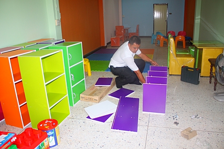 ESC welfare coordinator Samran Naepong assembles cabinets to store all the new items.
