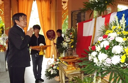 Deputy Mayor Ronakit Ekasingh presents a robe dedicated to the departed.