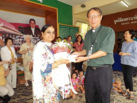Binota Banerjee presents a donation for the welfare of the orphans to Father Michael.