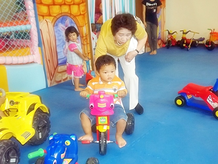 Kyoko Tanaka gives a gentle push to the little boy's tricycle.