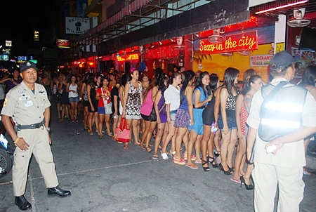 Bar workers are lined up on Soi 6 so that police can test them for drugs.