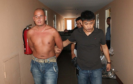 Police lead away Bernd Andreas Schmiedinghoff, accused of burglarizing a hotel room on Koh Chang and using stolen credit cards to withdraw cash from ATM machines.