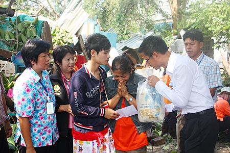 Pattaya Permanent Secretary Pakorn Sukhonthachat presents relief funds and supplies to Siriwan Kuwaentrai, grieving daughter of the deceased.