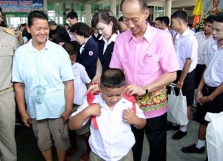 Gov. Khomsan Ekachai helps a youngster with his school backpack during the launch of Chonburi's mobile-services program.
