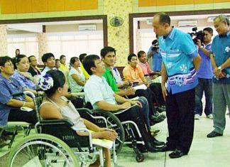 Gov. Khomsan Ekachai talks with disabled residents at Chalerm Prakiet Pavilion in Chonburi.