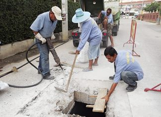 Sanitation workers clear drains and replace iron grates on Second Road in preparation of the coming rainy season.