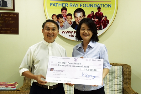 Vanvara Supongspun (right) presents a cheque for 25,000 baht to Father Pattarapong in aid of the Father Ray Foundation. The funds were raised at a recent party held at the Vanvaras German School located on Sukhumvit Road in Pattaya.