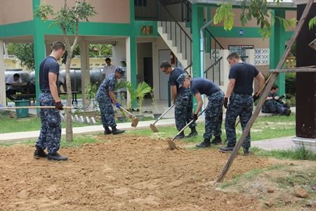 US Navy volunteers till the land so grass can be planted to make the surroundings greener.