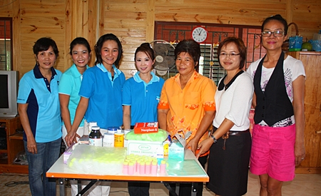 Praichit Jetapai (center) and members of the YWCA Bangkok-Pattaya Center present medicine to Boonchu Muangmaitong, principal of the Boonchu House for children with special needs.