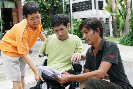 Den, center, receives the instructions for his new wheelchair.