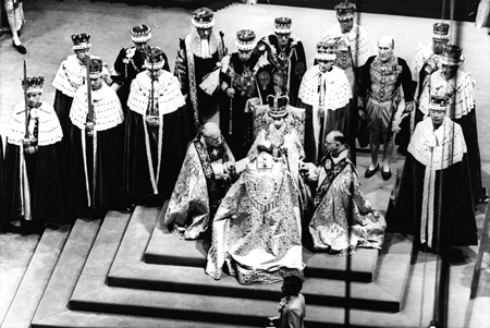 In this June 2, 1953 file photo, Britain's Queen Elizabeth II, seated on the throne, receives the fealty of the Archbishop of Canterbury, back to camera at center, the Bishop of Durham, left and the Bishop of Bath and Wells, during her coronation in Westminster Abbey, London. (AP Photo, File)