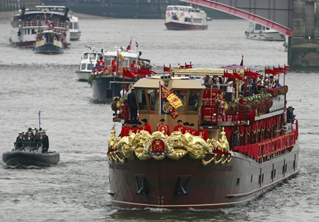 The Royal Barge after passing under Lambert Bridge during the Thames Diamond Jubilee River Pageant in London, Sunday, June 3. More than 1,000 boats sailed down the Thames on Sunday in a flotilla tribute to Queen Elizabeth II's 60 years on the throne that organizers are calling the biggest gathering on the river for 350 years. Despite cool, drizzly weather, hundreds of thousands of people lined the riverbanks in London, feting the British monarch whose longevity has given her the status of the nation's favorite grandmother. (AP Photo/Tim Hales)
