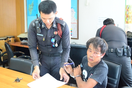 Sumrit Kalasin signs the police report after allegedly trying to rape his neighbor.