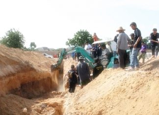 Rescue workers and police use a backhoe to search for buried construction worker Rattana Sujritphakdee.