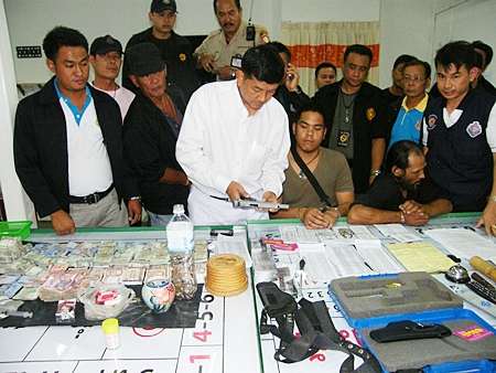 Banglamung District Chief Chawalit Saeng-Uthai inspects the confiscated handgun along with hundreds of thousands of baht, gambling slips and tables found during a raid on a Soi Buakaow home.