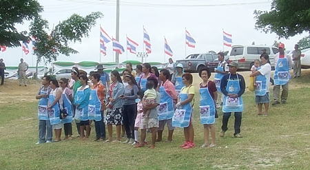 A group of Pong sub-district people near Mabprachan dam await the arrival of Prime Minister Yingluck Shinawatra and her cabinet on their tour of the dam development.