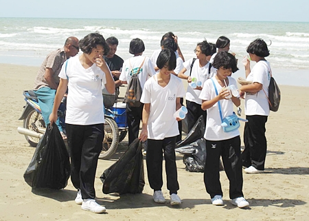 Students from a local school take a water break during their cleanup of Mae Rampung Beach in Rayong.