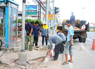 Workers repair damage caused by an accident at the Soi Siam Country Club intersection with Sukhumvit Road.
