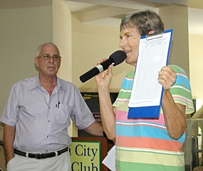 Pat Koester announces the sign up sheet for a trip to some of the older cultural sights of Samut Prakan, while MC Richard Silverberg looks on.