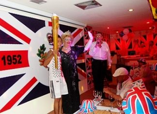 "The ""British queen from Pattaya,"" John, alias Dolly Sister, together with the relay runner is welcomed by manager David Kerridge."