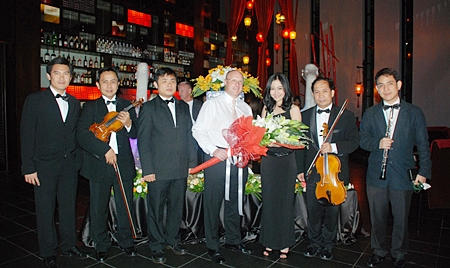 Amari Orchid Pattaya GM David Cumming (4th left) presents flowers to Kaewkan Chuenpennit, thanking her and the other members of the Bangkok Symphony Orchestra.