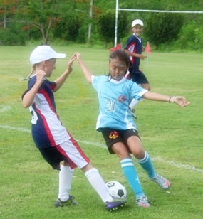 Jade gets stuck in and takes the ball from Garden School, Kuala Lumpur.