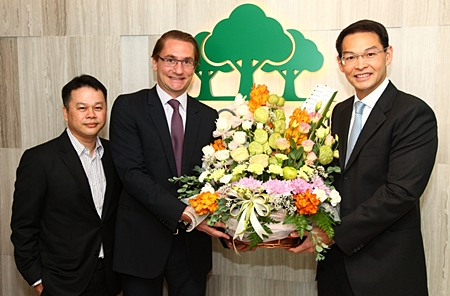 Hubert Viriot, center, Chief Executive Officer of Raimon Land PLC, and Chief Operating Officer Kitti Tungsriwong, left, receive a congratulatory bouquet from Chanitr Charnchainarong, right, the Executive Vice President of the Issuer & Listing Division of the Stock Exchange of Thailand (SET).