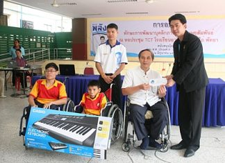 Porames Ngampiches, MP of Chonburi region 7, presents a cash donation and two electronic keyboards to Professor Udomchok Churat, director of Pattaya Redemptorist Vocational School for the Handicapped for use by the students in their studies and during recreation hours.
