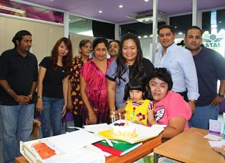 Business came to a stand still for a short spell at the Massic Travel hangar as the Malhotra family gathered around to wish Amita Malhotra (standing 3rd right) a Happy Birthday. (l-r) Vikrom, Hongsiri, Jasmeet, Malvinder, Marlowe, Prince and Ali. Foreground, Vicky is hugging the newest addition, baby Sujitra.