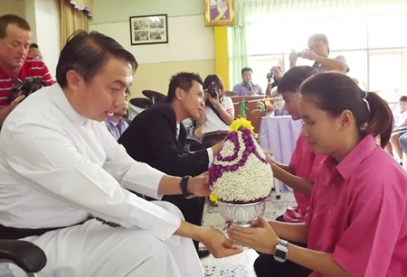 Father Pattarapong Peter Srivorakul, president of the Father Ray Foundation, receives flowers from a blind student.