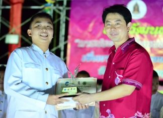 Chonburi MP, Poramet Ngampichet presents a trophy to Thaweesak Raksa from Mathayom 3 student from Pattaya School No. 9, the under-15 Thai traditional dancing contest winner.