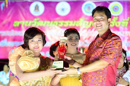 Mayor Itthiphol Kunplome presents the first prize trophy to singing contest winner Wanpen Boonrattavichai.