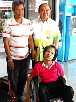 We provided Paew, a 14-year-old girl crippled from birth, with a bigger wheelchair, along with her ration of rice and milk. Her father stands on the left, next to the deputy mayor of Nongprue.