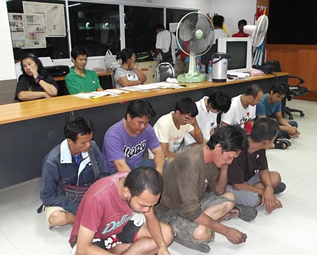 Nine drug suspects sit on the floor in front of the three suspects with the added charge of attempted bribery.
