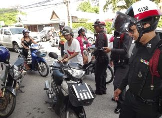 Police officers search for proper driving license and vehicle registrations at a roadblock set up on Pattaya 2nd Road.