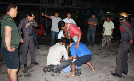 Police, unable to subdue the rock thrower, look on whilst civilians provide their own justice.