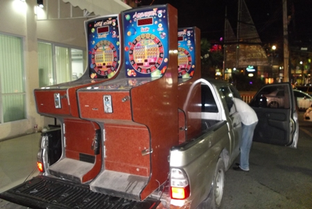 Police load up the confiscated slot machines to truck them away.