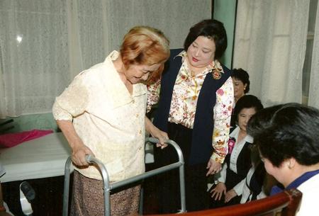 HRH Princess Soamsawalee graciously helps an elderly patient.
