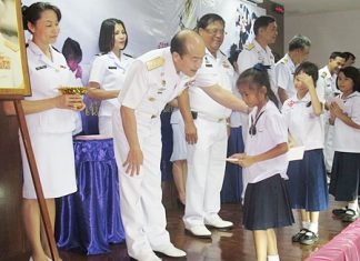 Top navy officers from the Royal Thai Navy's Ordinance Department hand out more than 700,000 baht in scholarships for children of enlisted personnel.
