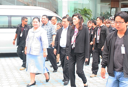 Prime Minister Yingluck Shinawatra arrives at the Royal Cliff with Tourism and Sports Minister Sukumol Kunplome.
