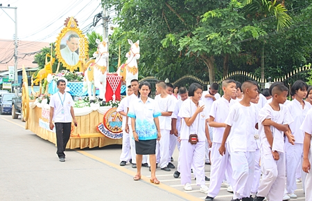 Teachers and students of Wat Suthawat School march in the candle parade to present it to the abbot of Wat Suthawat.