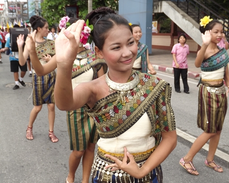 Women dressed in Thai traditional costumes performing ancient Thai dances are another tradition of the candle parade that has been preserved.