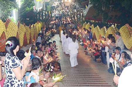 Buddhist monks and nuns walk down the stairs to join in candle parade at Wat Phra Yai.