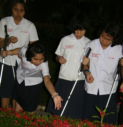 The blind students sprinkle rose petals on Father Ray's final resting place.