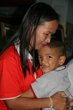 A little boy from the Children's Village seems happy in the arms of his mother.
